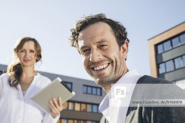 Porträt eines lächelnden Geschäftsmannes mit Kollegin im Hintergrund