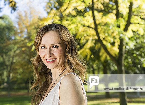 Porträt einer lächelnden Frau im Park