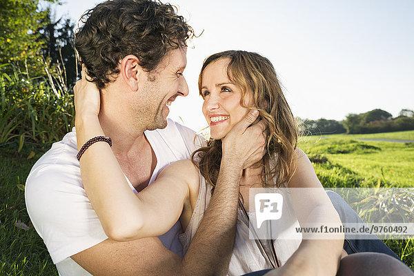 Glückliches Paar von Angesicht zu Angesicht in der Natur sitzend