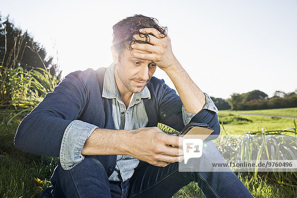 Man sitting on a meadow reading SMS