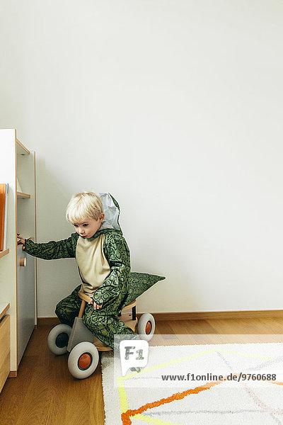 Kleiner Junge im Dinosaurierkostüm sitzend auf Spielzeugauto zu Hause