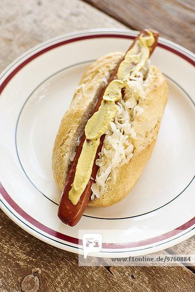 Veganer Hot Dog mit Sauerkraut und Senf auf dem Teller Veganer Hot Dog mit Sauerkraut und Senf auf dem Teller