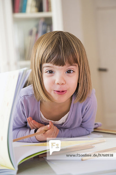 Portrait of little girl with coloured pencils