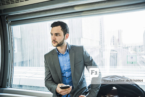 Young businessman with cell phone in underground train