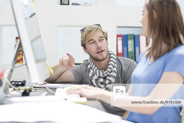 Kreative Büromenschen diskutieren über die Arbeit am Computer