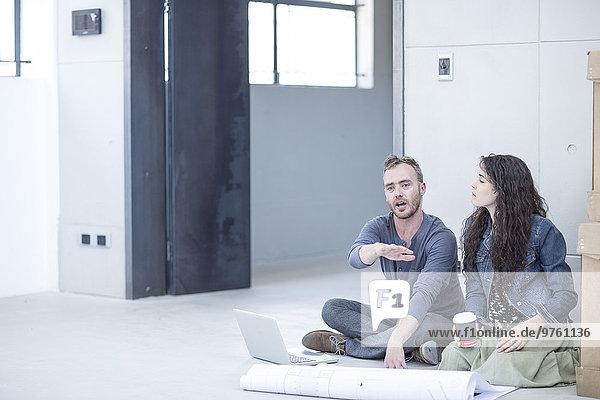 Kreative Büromenschen sitzen mit Bauplan und Boxen