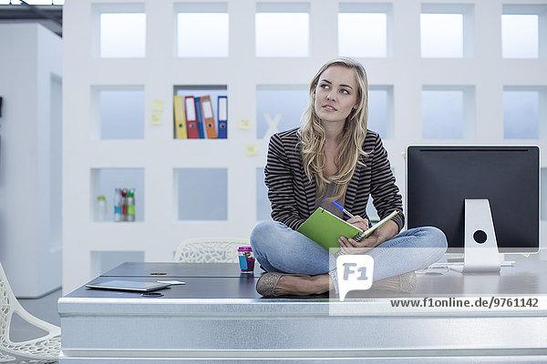 Kreative Bürofrau auf dem Schreibtisch mit einem Tagesplaner