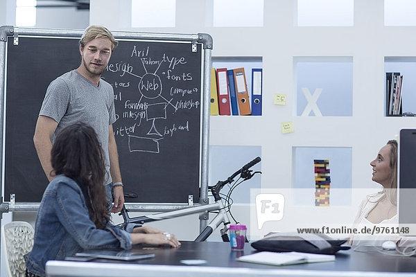 Kreative Bürobesprechung und Schreiben auf einer Tafel