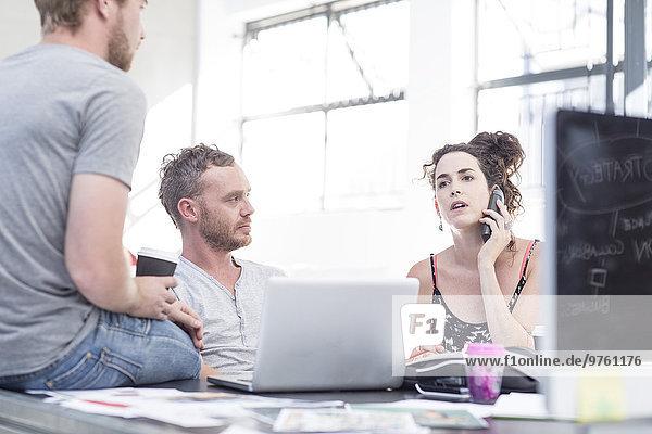 Kreative Büromenschen mit lockerer Teambesprechung und Telefonieren