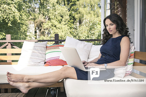 Porträt einer Frau mit Laptop auf dem Balkon