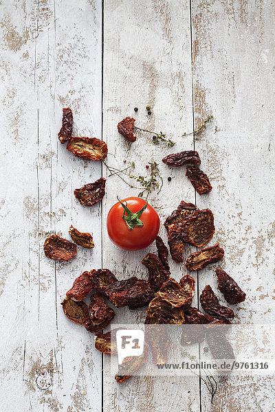 Getrocknete und frische Tomaten auf Holz
