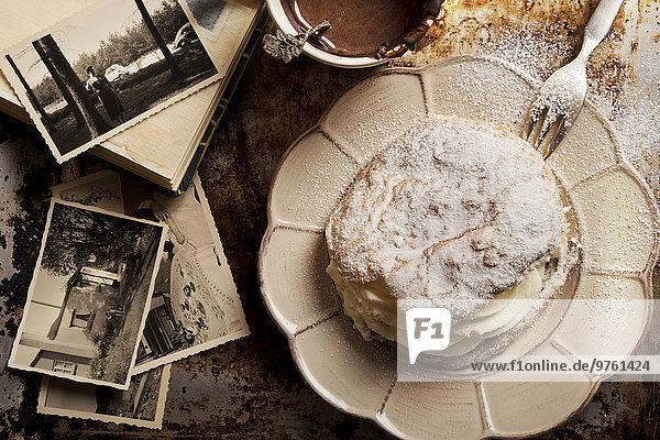 Geschnittenes Brötchen gefüllt mit Schlagsahne  Tasse heißer Schokolade und alten Fotografien
