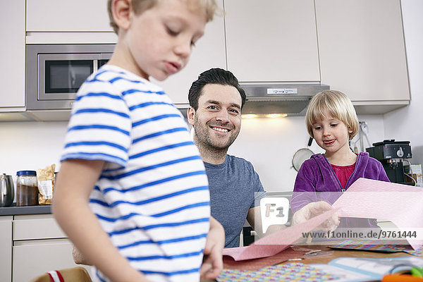 Vater bastelt in der Küche mit Sohn und Tochter