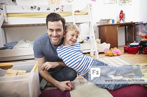 Vater und Sohn spielen zusammen im Kinderzimmer