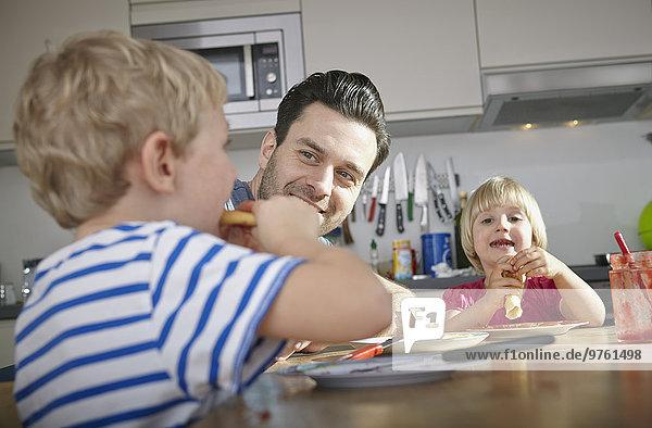 Vater und Kinder beim Frühstücken in der Küche