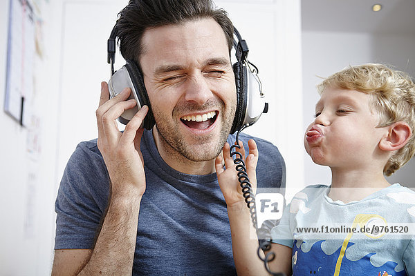 Father and son listening to music with headphones
