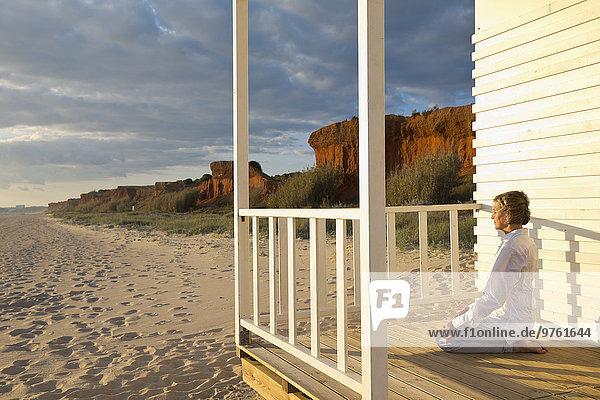 Portugal  Algarve  Frau beim Yoga am Strandhaus bei Sonnenuntergang