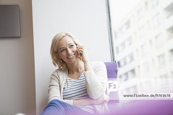 Portrait einer lächelnden Frau beim Telefonieren mit Smartphone am Fenster