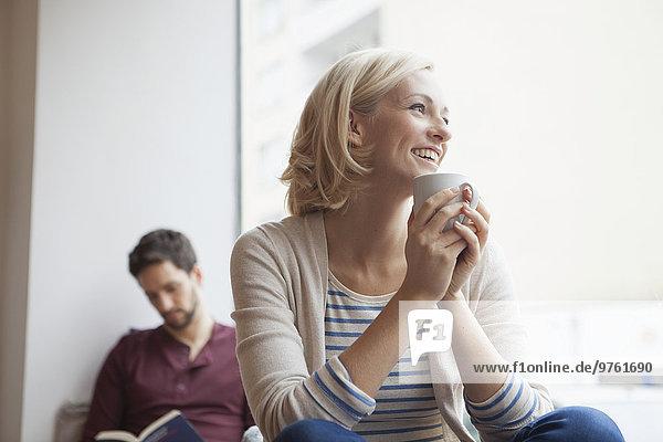 Porträt einer glücklichen Frau  die sich bei einer Tasse Tee entspannt.