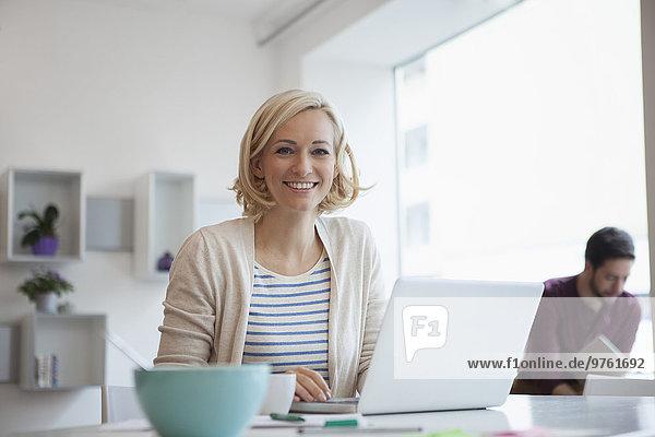 Porträt einer lächelnden Frau bei der Arbeit mit dem Laptop im Home Office