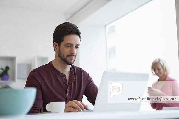 Mann arbeitet mit Laptop im Home-Office
