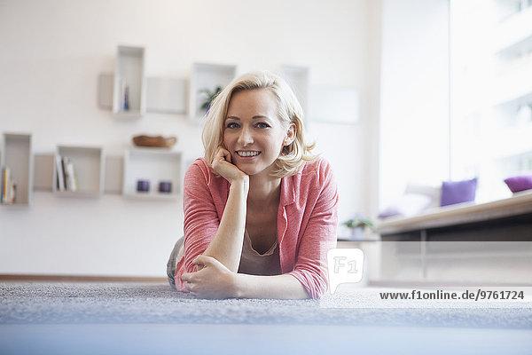 Porträt einer lächelnden Frau  die im Wohnzimmer auf einem Teppich liegt.