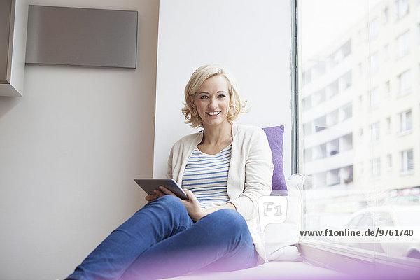 Porträt einer lächelnden Frau mit digitalem Tablett am Fenster sitzend