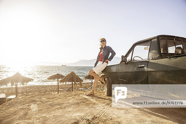 Greece  Crete  Matala  woman leaning against pickup truck at the beach