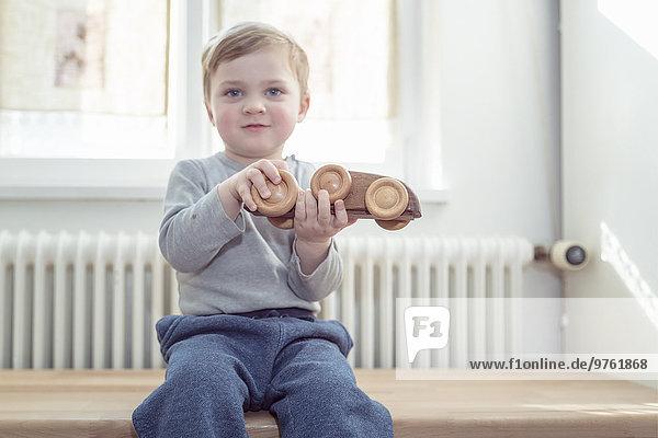 Kleiner Junge spielt zu Hause mit Holzspielzeug