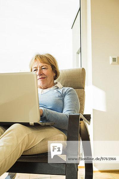 Seniorin zu Hause mit Laptop