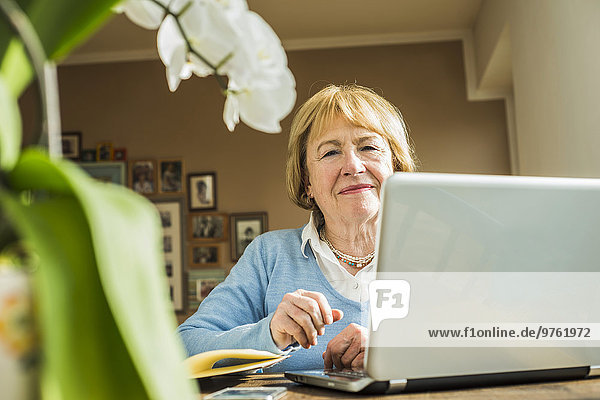 Porträt einer älteren Frau zu Hause mit Laptop