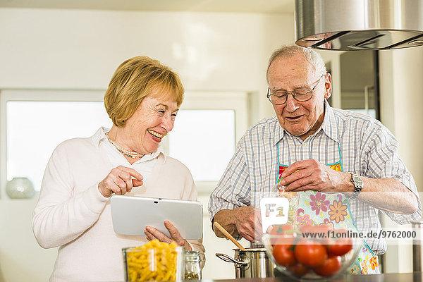 Seniorenpaar mit digitalem Tablettenkochen in der Küche