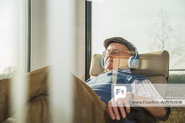 Senior Mann zu Hause entspannt mit Kopfhörer