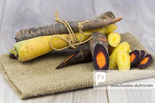 Geschnittene und ganze Bio Purple Haze und gelbe Karotten auf Jute