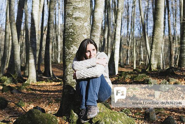 Frau auf einem Felsen im Buchenwald sitzend
