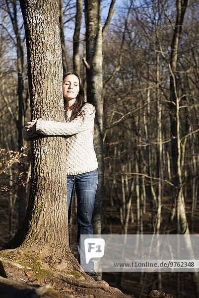 Frau umarmt eine Buche im Wald