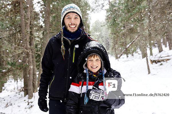 Glücklicher Mann und Junge im Wald beim Schneefall