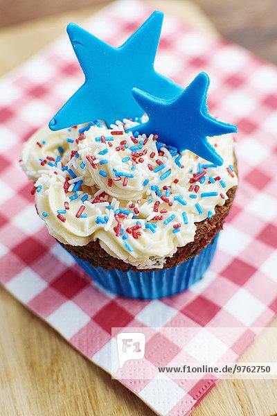 Törtchen mit weißer Glasur  bunten Streuseln und einem blauen Stern aus Fondant Törtchen mit weißer Glasur, bunten Streuseln und einem blauen Stern aus Fondant