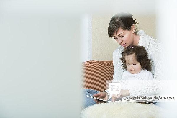 Frau und Tochter beim Betrachten des Bilderbuchs