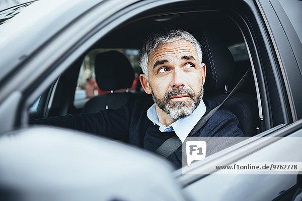 Mann im Auto schaut nach oben