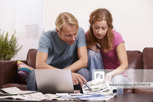 Paar mit Laptop und Zeitschrift auf der Couch