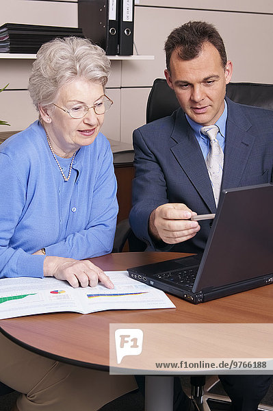 Berater mit Laptop im Gespräch mit Seniorin