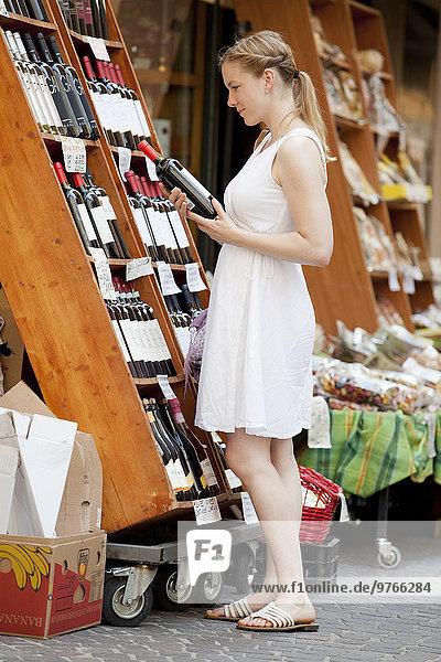 Frau kauft Wein in der Stadt ein  Garda  Italien