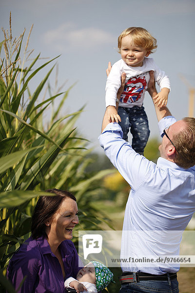 Glückliche Familie an einem Maisfeld