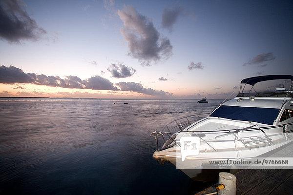 Motorboot am Bootssteg bei Sonnenuntergang auf den Malediven