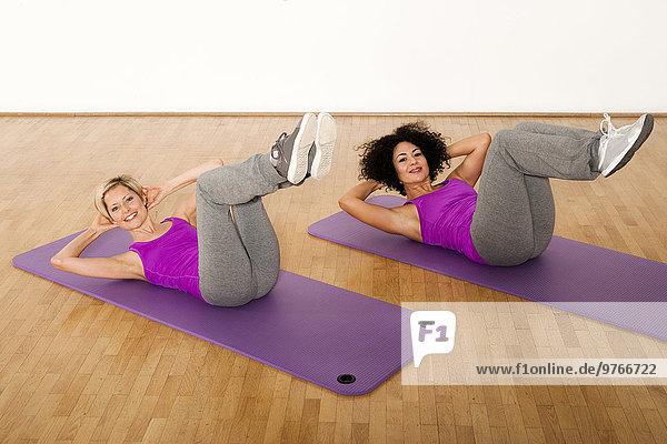 Zwei Frauen trainieren auf Gymnastikmatten in einem Fitnessstudio