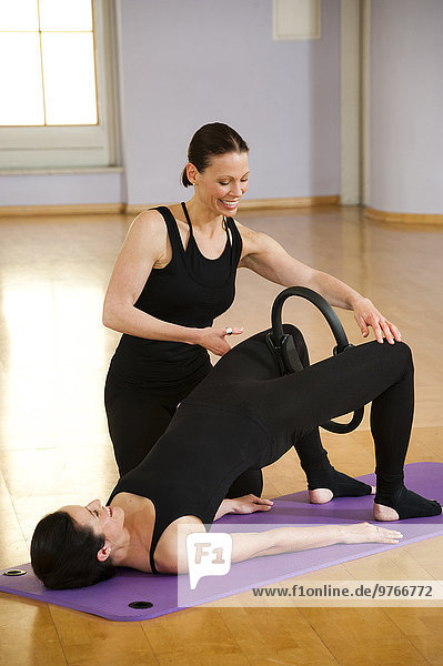 Two women practicing with pilates circles in a health club