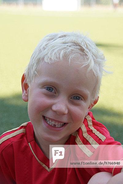 Lächelnder blonder Junge im Fußballtrikot  Porträt