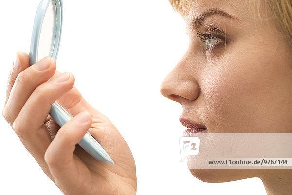 Junge Frau schaut in einen Handspiegel  close-up