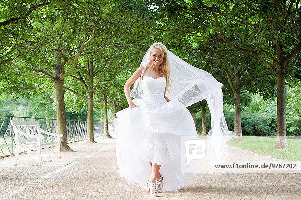Junge Frau im Brautkleid auf einer Allee